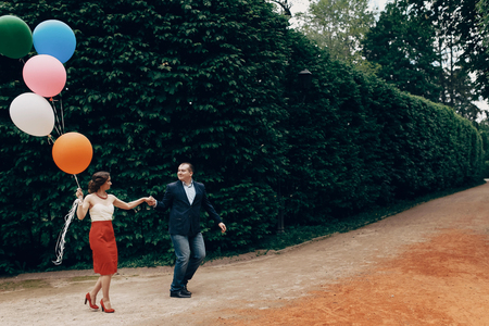 Photo for Cheerful groom in stylish clothes leading happy bride by her hand in a park, newlywed couple on a walk at the carnival with colorful balloons, fun honeymoon concept - Royalty Free Image