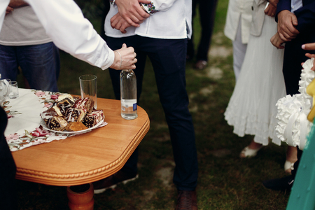 Photo for Traditional ukrainian wedding table for guests before ceremony, stylish man drinking and toasting vodka drinks near wooden table with tasty deserts, outdoors - Royalty Free Image