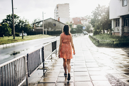 stylish hipster woman walking in sunny rainy street in summer under rain with big drops. young girl enjoying moment. space for text. joyful moments. summer relax. back view