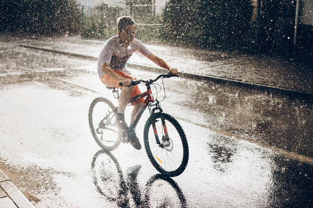 Foto de young boy riding bicycle in rainy street in sunshine, summer moments. space for text. atmospheric moment. cycling and activity. stylish hipster having fun under rain - Imagen libre de derechos