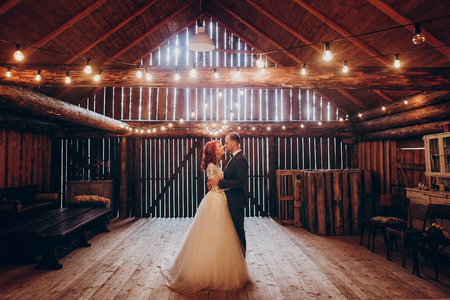Photo for stylish groom and happy bride hugging under retro bulbs lights in wooden barn. rustic wedding concept, space for text. newlyweds couple embracing, sensual romantic moment - Royalty Free Image