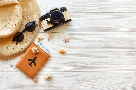 Foto de summer travel vacation concept flat lay, space for text. photo camera passport  money plane hat  and sunglasses and shells on white wooden background top view. hello summer. wanderlust - Imagen libre de derechos