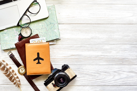 Foto de travel and wanderlust concept, planning summer vacation background flat lay, space for text. map compass photo camera sunglasses wallet watch laptop on white wooden table top view - Imagen libre de derechos