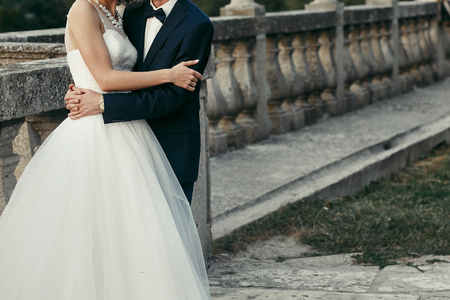 Photo for elegant bride and groom gently hugging. wedding couple embracing at old castle in the evening. space for text. man in classic suit with bow tie and woman in white dress with pearls - Royalty Free Image
