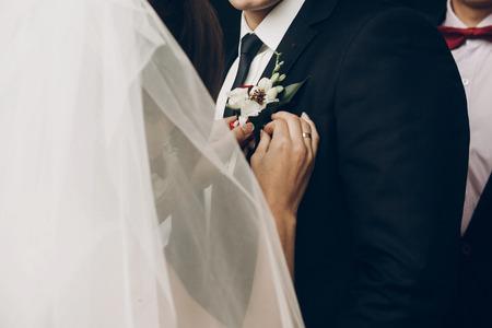 Foto de bride putting on groom boutonniere of red white flowers close up on jacket - Imagen libre de derechos
