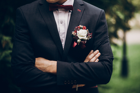 Foto de groom or groomsmen closeup, bow tie and boutonniere on suit, confident stylish man - Imagen libre de derechos