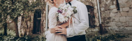 Foto de stylish wedding couple with bouquet. modern bride and groom holding fashionable bouquet at old  castle. fine art wedding photo, romantic moment, long edge - Imagen libre de derechos