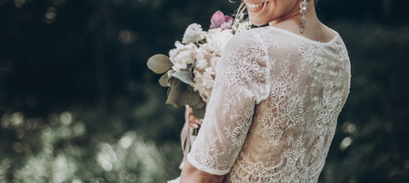 Foto de stylish wedding bride with bouquet and amazing modern dress. bride posing and smiling in sunny garden, lips and earrings close up. fine art wedding photo, romantic moment, long edge - Imagen libre de derechos
