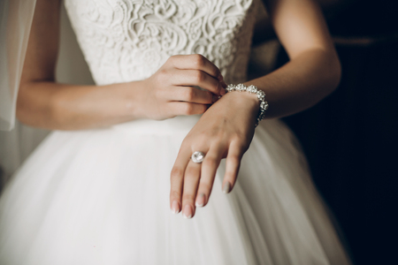 Foto de bride putting on luxury bracelet on hand in the morning, getting ready - Imagen libre de derechos