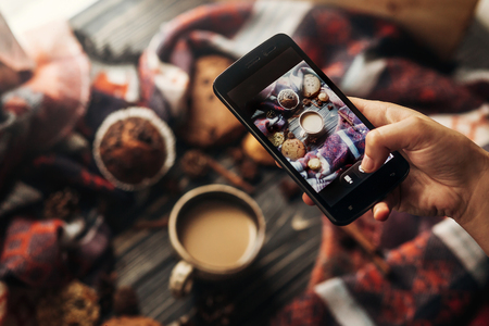 Photo pour hand holding phone taking photo of stylish winter flat lay coffee cookies and spices on wooden rustic background. cozy mood autumn - image libre de droit