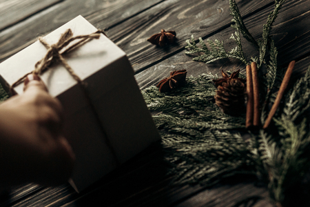 Foto de hands holding christmas simple present box and giving on stylish rustic wooden background with space for text. greeting card concept. seasonal greetings for winter holidays - Imagen libre de derechos