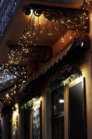 Photo for luxury decorated store front with garland lights in european city street at winter seasonal holidays - Royalty Free Image