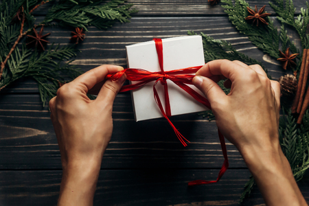 Foto de hands wrapping christmas present with red ribbon on stylish wooden background flat lay with green branches. space for text. greeting card concept. seasonal greetings for winter holidays - Imagen libre de derechos