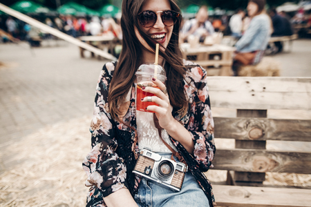 Foto de happy stylish hipster woman in sunglasses with lemonade. boho girl in denim and bohemian clothes, holding cocktail sitting on wooden bench at street food festival. summertime. summer vacation - Imagen libre de derechos