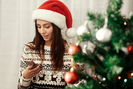 Foto de stylish woman holding phone looking at screen at christmas tree lights. wearing sweater reindeers and santa hat smiling. seasonal greetings concept. space for text - Imagen libre de derechos