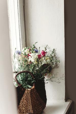 Foto de wildflowers in wicker bag on rustic white window. colorful flowers in brown basket in sunlight, space for text. rural atmospheric moment. unusual summer picture - Imagen libre de derechos