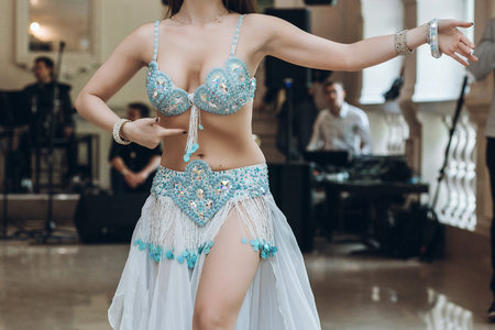 Photo for eastern dancing. sexy woman in blue costume performing eastern dance. belly dancer. beautiful woman dancing at wedding reception in restaurant - Royalty Free Image