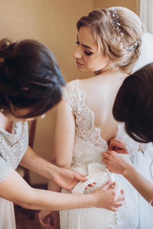 Photo pour Beautiful bridesmaids help put on wedding dress on gorgeous blonde bride in luxury hotel room morning before the wedding - image libre de droit