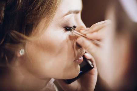 Photo pour make up. bride getting on her make-up on by professional artist, morning preparation. beautiful bride in robe talking on phone and hand with tweezers putting on eyelashes - image libre de droit