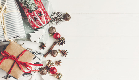 Foto de christmas flat lay. wrapped presents with ornaments  car toy and pine cones anise on rustic white wooden background top view, space for text. stylish gifts. seasonal greetings. happy holidays - Imagen libre de derechos