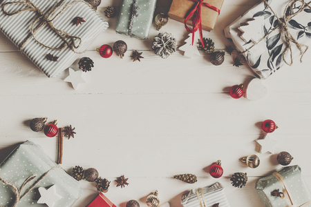 Photo pour christmas flat lay mock up. present boxes with ornaments and pine cones anise on white wooden background top view, space for text. stylish wrapped gifts. seasonal greetings card. happy holidays - image libre de droit