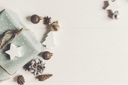 Foto de merry christmas concept, flat lay. stylish presents and gifts with ornaments cones anise on rustic white wood top view, space for text. seasonal greetings. happy holidays. xmas card - Imagen libre de derechos