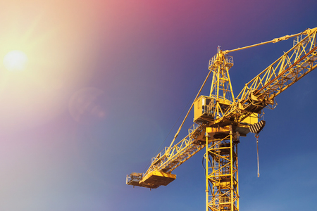 Foto de Construction crane tower in sun light on background of blue sky. - Imagen libre de derechos