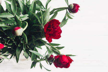 Photo for beautiful red peonies blooming bouquet on white wooden rustic background, flat lay. - Royalty Free Image