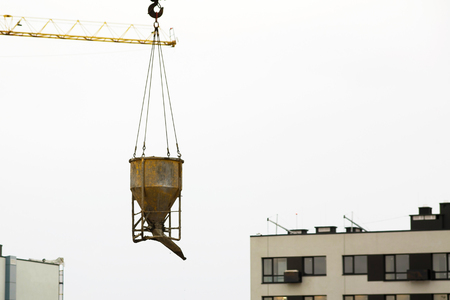 Foto per crane lifting bucket of cement and transporting at construction site at new building skyscrapers. Industrial landscape with cranes, building steel and concrete - Immagine Royalty Free