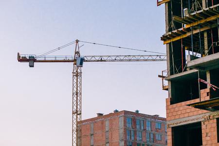 Foto de Crane and building construction site on background of  sky. Industrial landscape with silhouettes of cranes and building bricks over sunlight. space for text . steel and concrete . development - Imagen libre de derechos
