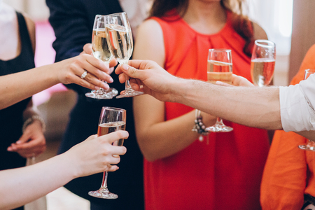 Foto de group of elegant people holding glasses of champagne at luxury wedding reception. people hands toasting and cheering with drinks at social events.  christmas celebration - Imagen libre de derechos