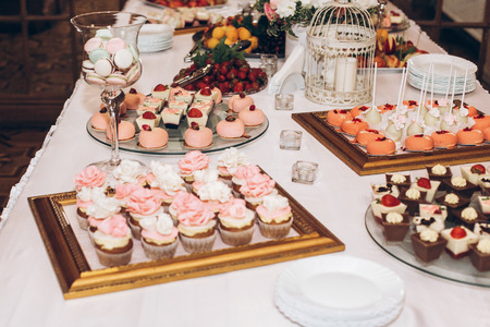 Photo for delicious candy,sweets,cupcakes,pops decorated with flowers on table at wedding reception. candy bar. tasty pink sweets for celebrations events and showers. luxury stylish catering - Royalty Free Image