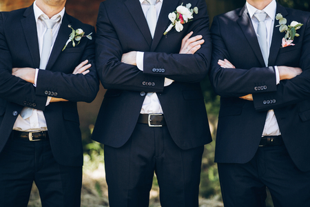 Photo for stylish groom in suit posing with groomsmen in garden on wedding day. luxury men in  rich outfits standing together. friendship - Royalty Free Image