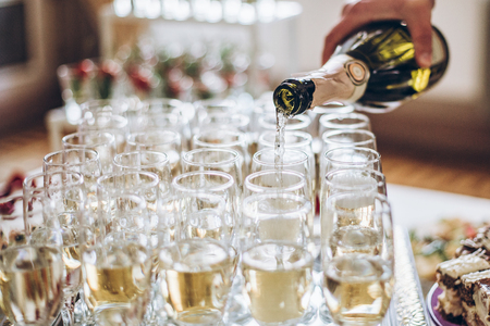 Photo for champagne golden glasses. waiter pouring champagne in stylish glasses at luxury wedding reception. rich celebration. - Royalty Free Image