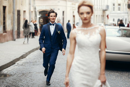 Photo pour stylish bride walking and groom running after her in city street. happy luxury wedding couple having fun and dancing . romantic  moment. - image libre de droit