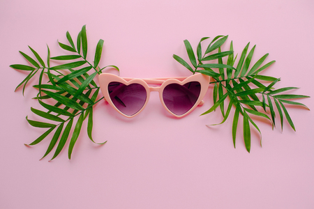 Photo pour summer vacation concept. stylish pink sunglasses in heart shape and green palm leaves on pink background, flat lay. space for text.  time to travel concept and relax. holidays - image libre de droit
