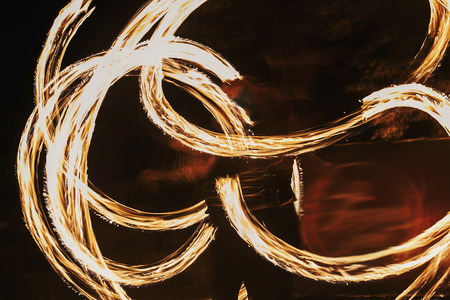 Foto de Fire dancers swing, spinning fire and man juggling with bright sparks in the night. fire show performance and entertainment. amazing fire show at night at festival or wedding party. - Imagen libre de derechos