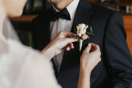 Foto de beautiful bride putting on stylish simple boutonniere with roses on groom black suit. wedding morning preparations - Imagen libre de derechos
