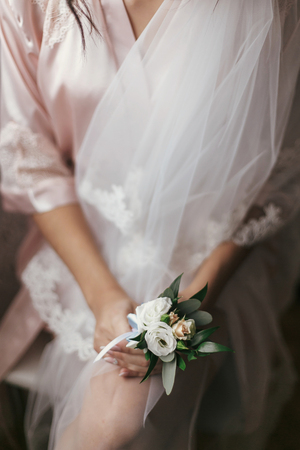 Photo pour gorgeous bride holding boutonniere, sitting in robe near window. beautiful woman getting ready for wedding day, holding flowers. girl legs and veil. sensual moment. boudoir - image libre de droit