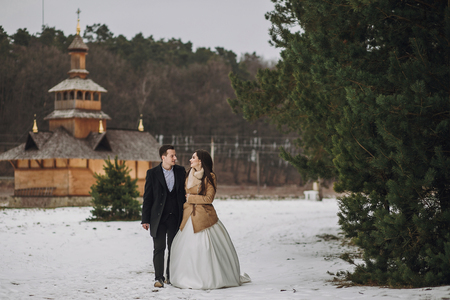 Photo pour gorgeous bride and groom walking at wooden church in autumn forest. happy newlywed couple hugging in woods after holy wedding ceremony, romantic tender moment - image libre de droit
