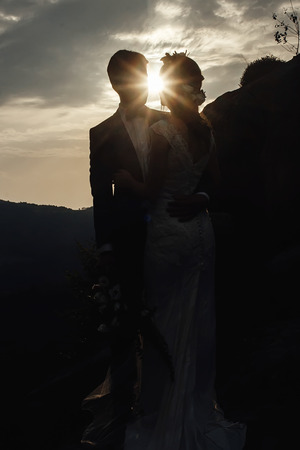 Photo for silhouettes stylish gorgeous couple newlyweds kissing  on the rocks in the mountains in the sunset - Royalty Free Image