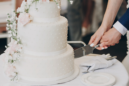 Foto de bride and groom holding knife and cutting stylish white wedding cake with flowers. modern big wedding cake with pink and white roses. luxury catering in restaurant. wedding reception - Imagen libre de derechos