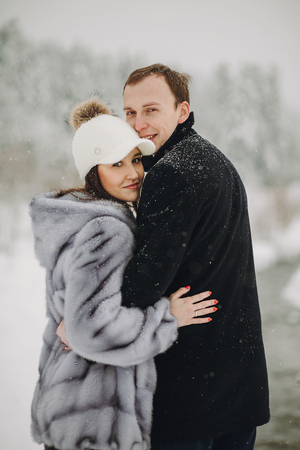 Foto de Stylish couple in love hugging in snowy mountains. Portraits of happy family gently embracing and smiling in winter mountains and forest. Holiday getaway together - Imagen libre de derechos