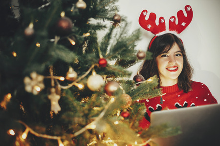 christmas shopping online concept and  freelance. beautiful happy girl in reindeer antlers sitting with laptop at golden beautiful christmas tree with lights and presents in festive room.