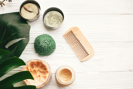 Photo for Natural eco friendly solid shampoo bar, wooden brush,  deodorant cream, scrub and konjaku sponge on white wood with green monstera leaves. Zero waste products plastic free - Royalty Free Image
