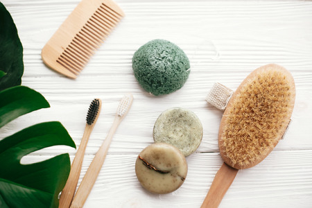 Photo for Zero waste flat lay. Natural solid shampoo bar, bamboo toothbrushes, wooden brush,  deodorant cream and konjaku sponge on white wood with green monstera leaves. Eco products plastic free - Royalty Free Image