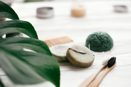 Photo pour Zero waste solid shampoo bar, bamboo toothbrushes, wooden brush and konjaku sponge on white wood with green monstera leaves. Eco friendly natural products plastic free - image libre de droit