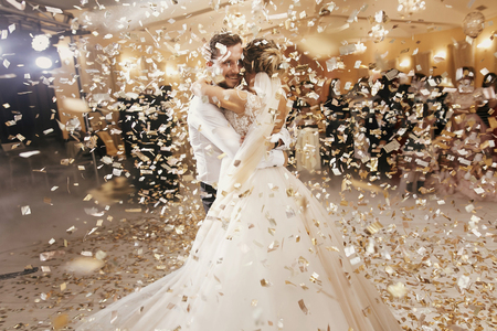 Foto de Gorgeous bride and stylish groom dancing under golden confetti at wedding reception. Happy wedding couple performing first dance in restaurant. Romantic moments - Imagen libre de derechos
