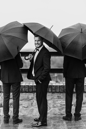 Photo pour Stylish groom and groomsmen standing under black umbrella and posing. Confident man in suit holding umbrella in rainy outdoors. Rich Businessman and protection concept - image libre de droit