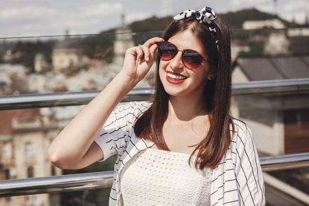 Photo pour Beautiful stylish young woman in sunglasses, retro dress and headband relaxing on roof in european city street. Happy hipster girl smiling and enjoying summer time in Lviv. Copy space - image libre de droit